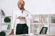 serious african american businesswoman with short hair standing near table in modern office