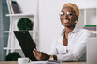 happy african american businesswoman holding clipboard in modern office
