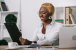 cheerful african american businesswoman holding clipboard in modern office