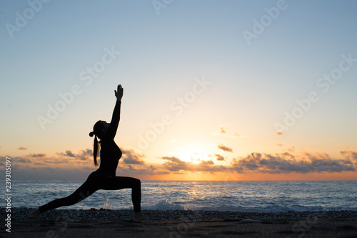 Wall mural Human silhouette doing yoga on the beach in front of rising sun