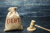 A bag of money and the word Debt and the hammer of the judge. Payment of taxes and of debt to the state. Concept of financial crisis and problems. Risk management. Debt exemption. Credit and loan