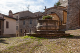 A travertine well in the centre of ancient square named after the painter Vecchietta in medieval town of Castiglione d'Orcia, Italy