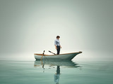 The man is in a boat and admire the lake in the fog.