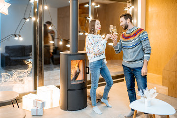 Young couple in sweaters celebrating winter holidays standing with sparkling wine in the modern house with fire place