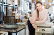 Woman buyer standing in furniture shopping room near chest of drawers