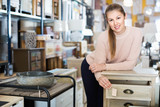 Woman buyer standing in furniture shopping room near chest of drawers - 239382475