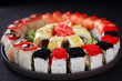 food art, traditional japanese seafood, restaurant menu photo. great colorful set of fresh maki sushi rolls served in black porcelain plate
