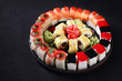 sushi, japanese food, deluxe restaurant menu, delicious traditional seafood. maki rolls set with salmon and caviar, served on black plate, close up