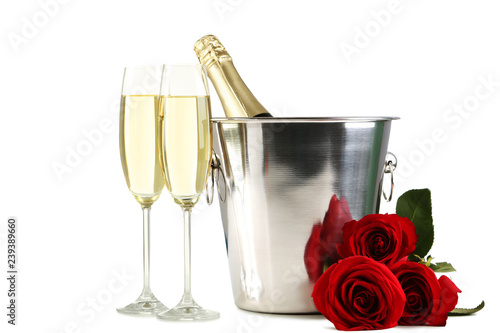 Champagne Bottle In Bucket With Glasses And Bouquet Of Red Roses On