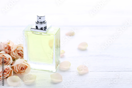 Perfume bottle with roses on white wooden table