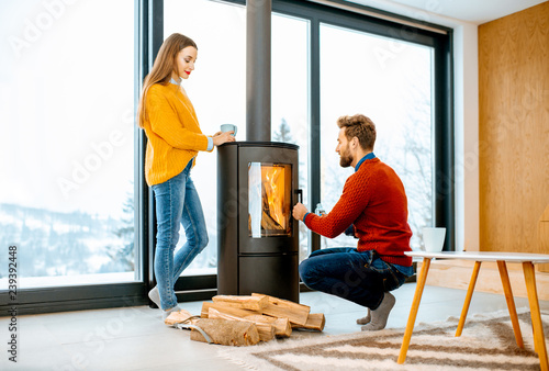Leinwanddruck Bild Young couple dressed in bright sweaters warming up near the fireplace in the modern house in the mountains during the winter