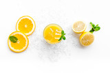 Orange juice with ice cubes. Juice in glass near cut orange and lemon, crushed ice, green mint on white background top view