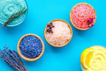 Aromas of bath salt. Lemon, coffee, rosemary, rose, lavender near bowls with colorful bath salt on blue background top view © 9dreamstudio