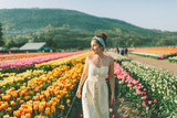 A beautiful woman walking through a field of tulips in Spring. © Crystal Sing