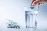Magnesium pills and cup of clear water on blue white background