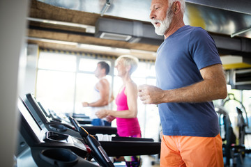 Happy senior people running together on treadmills in gym. © nd3000