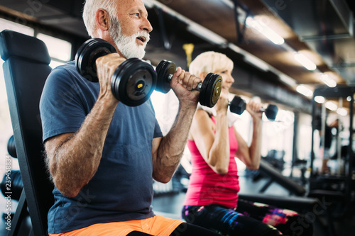 Leinwanddruck Bild Senior fit man and woman doing exercises in gym to stay healthy