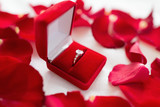 jewelry, proposal and romantic concept - diamond ring in red velvet gift box on bed sheet and rose petals