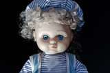 Girl doll with bright blue eyes. Sitting doll in blue clothes