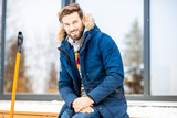 Portrait of a handsome man in winter clothes sitting on the terrace of the modern house - 239478437