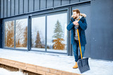 Portrait of a man in winter clothes standing with snow shovel on the terrace of the building in the mountains - 239497454