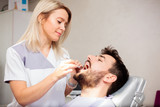 Beautiful young blond haired female dentist examining male patient's teeth in a dental clinic. Health care and medicine concept