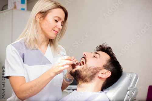 obraz PCV Beautiful young blond haired female dentist examining male patient's teeth in a dental clinic. Health care and medicine concept