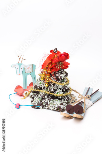 christmas tree made of cookies, covered with white black chocolate, with toy skiing, deer