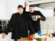 Men professionals are cooking salad with emotions in the kitchen