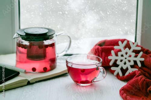 Winter cozy cranberry tea in front of window, snow, sweater. Lazy weekend, love, comfort