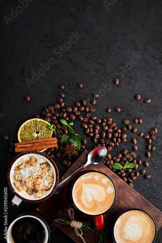 Cappuccino with milk and nuts and marshmallow. On a black stone background. Top view. Free copy space.