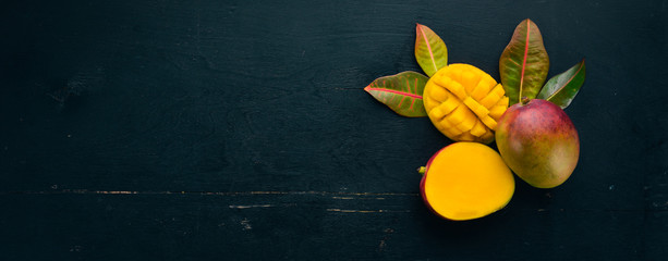 Mango with leaves on a black wooden background. Tropical Fruits. Top view. free space for your text. © Yaruniv-Studio