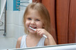 A little girl with blond hair brushing her teeth. The child is smiling at the reflection in the mirror.