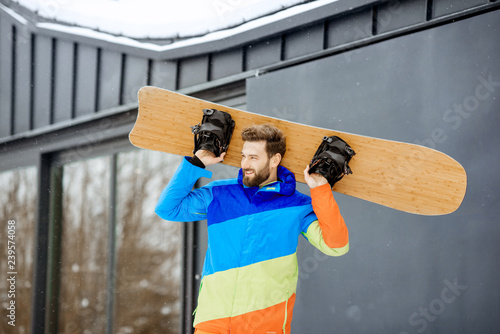 obraz lub plakat Man in ski suit with snowboard near the modern house or hotel in the mountains