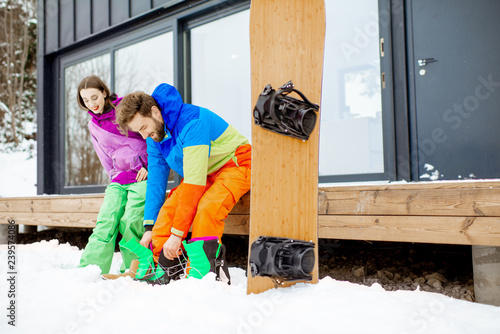 Young couple in ski suits preparing for snowboarding sitting on the terrace of the modern house in the mountains
