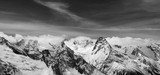 Black and white panorama of snowy winter mountain and sky with clouds