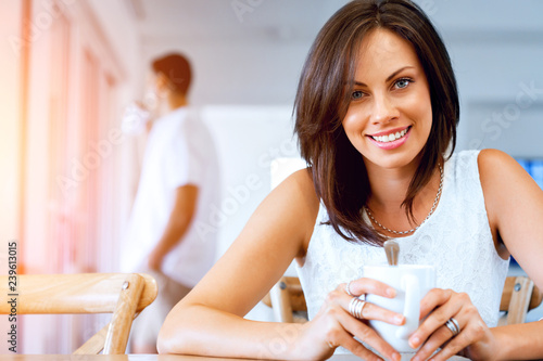 Leinwanddruck Bild Happy young woman with cup of tea or coffee