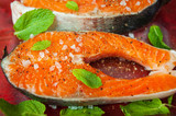 Raw trout steaks. Red fish with lemon balm leaves and coarse salt. Close-up - 239623087