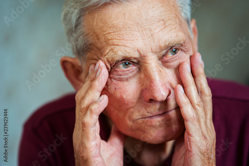 Leinwandbild Motiv Age-related dementia. Health problems in age. Sad elderly european man holding his head. Migraine