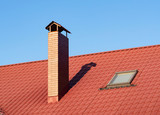 Close up of brick chimney and skylight on the metal tile roof