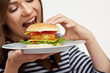 portrait of woman eating burger on white plate.
