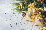 Gold bags with Christmas gifts on the background of Christmas trees and decorations gray background. New year greetings concept. - 239643470