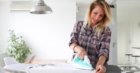 Beautiful young woman is ironing clothes at home © nd3000