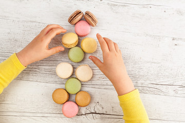 Girl's hands arranging macarons on white rustic wooden table © Greg Brave