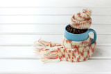 blue cup full of roasted coffee beans, wrapped in a pink scarf and a cap / warming natural coffee