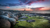 Big round rocks and stones with green seaweed at the coast of Easkey Beach, Ireland, with in the background the ruin of a castle-tower under the blue and purple sky after sunset