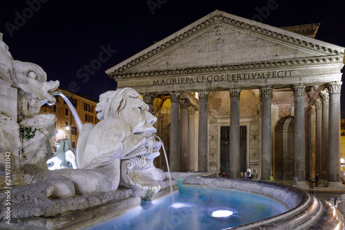 Pantheon and the fountain of Piazza della Rotonda. First floor of the fountain and in the background the facade of the Pantheon of Rome. with its marble sculptures and water jets.