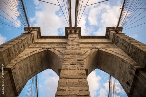 mata magnetyczna Scenic abstract view of the steel cables and textured bricks of the iconic stone arch tower of the Brooklyn Bridge under soft blue sky with sunset clouds