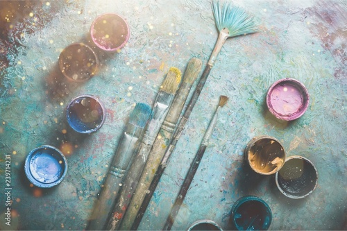 Artist paint brushes and paint cans of paint over bright