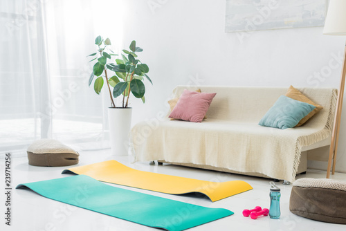 living room with blue and yellow fitness mats and sport equipment on floor